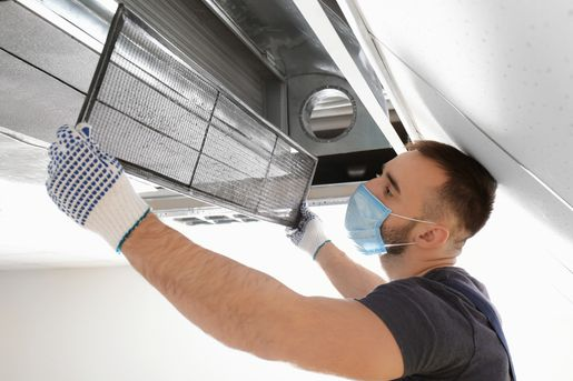 Expert cleaning an air conditioner unit